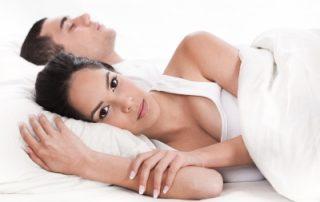 woman lying awake next to sleeping partner