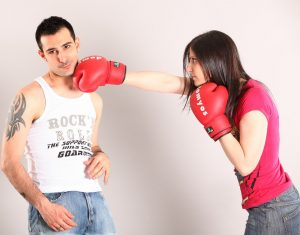 woman with boxing gloves giving partner a right hook