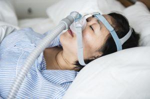 woman-in-bed-wearing-sleep-apnea-apparatus