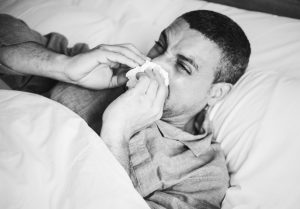 man-in-bed-blowing-nose