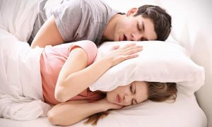 woman-covering-ears-with-pillow-snoring-partner