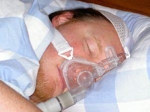 sleeping man wearing cpap device