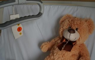teddy bear lying in hospital bed