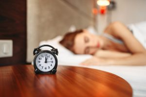 Sleeping woman with alarm clock on table in foreground