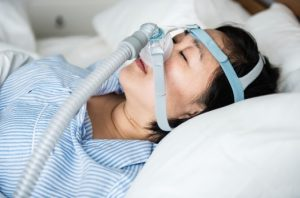 woman laying in bed with CPAP device
