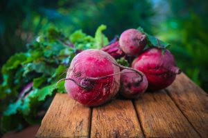 Bundle of beets with green tops on wooden table