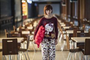 Woman in pyjamas walking in classroom with pillow under right arm