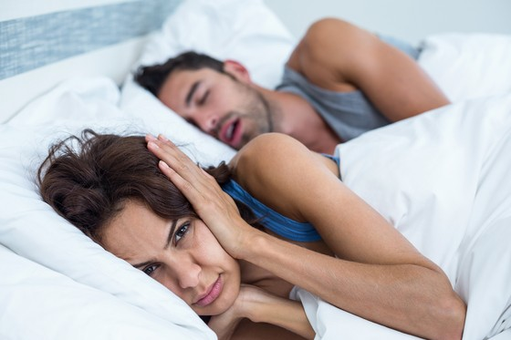 woman covering ears to drown out snoring partner