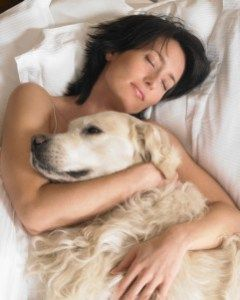 woman asleep with labrador in her arms