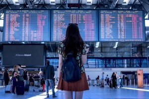 woman looking at departure board at airport