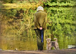 woman standing by pond with dog