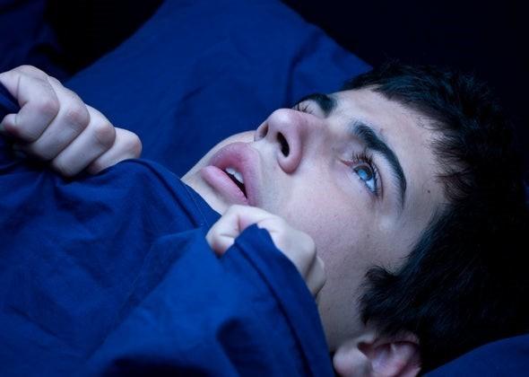 Boy lying awake clutching covers to chin