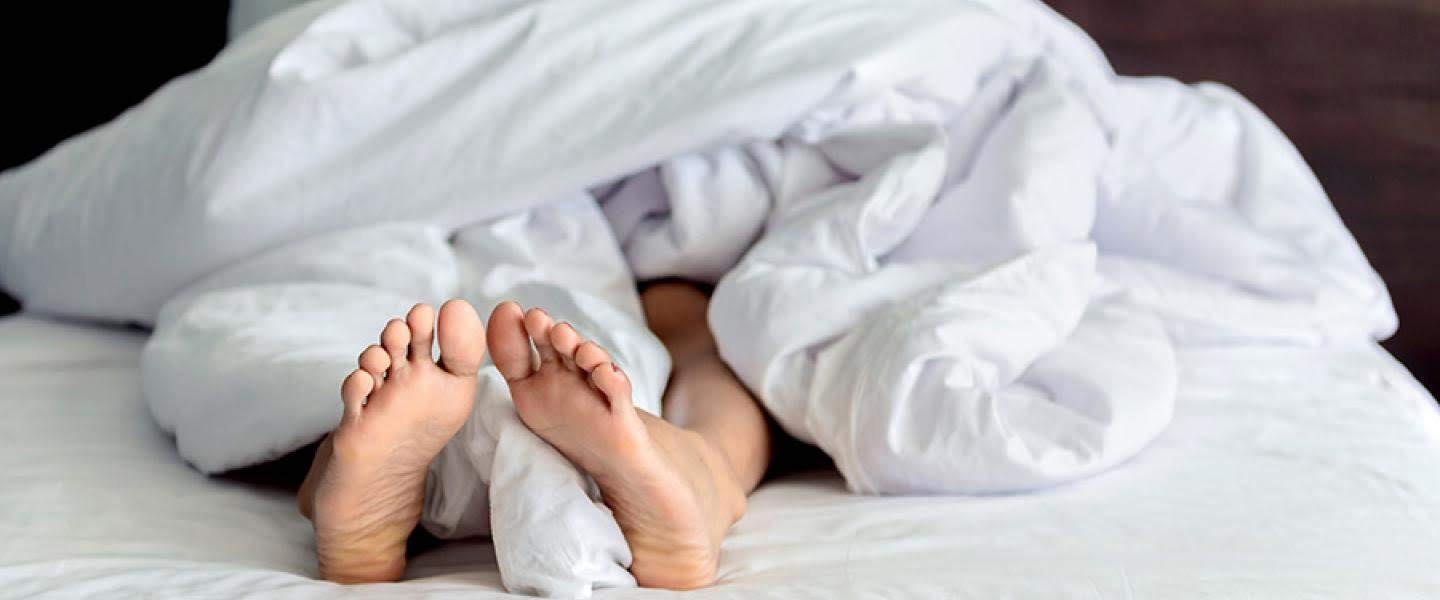 pair of feet protruding from bedclothes