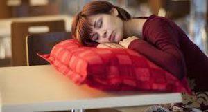 woman with pillow sleeping in cafeteria