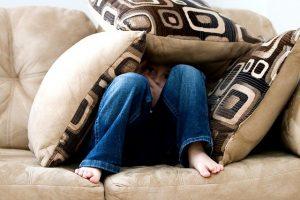 boy sitting on sofa with three cushions covering him