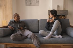 Couple on couch talking and smiling