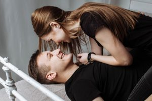 women bent over smiling man on bed