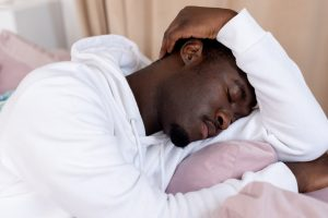 man sleeping with arm on head