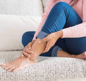 woman on couch massaging left leg
