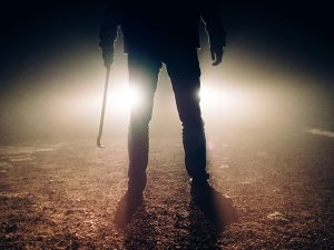Image of figure holding crowbar silhouetted by car headlights