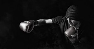 B/W photo of man in knitted cap throwing punch with right hand