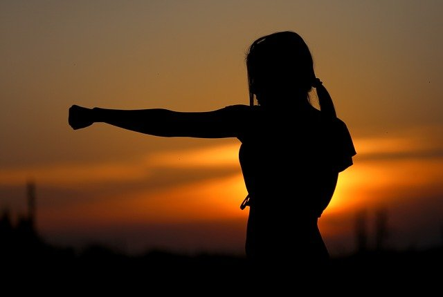 woman in silhouette against setting sun in karate stance